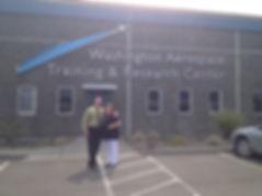 Larry Clupfh, Linda Lanham, in front of WATR, Washington Aerospace Training & Research Center