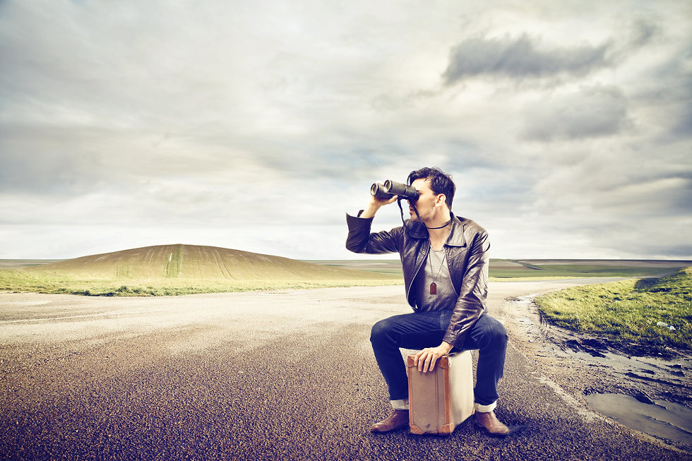 young man looks with binoculars sitting