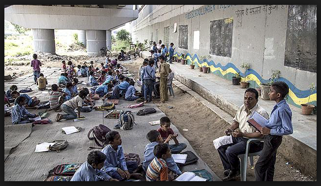 Students learning under a highway in India.