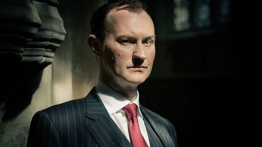 Close up of Mark Gatiss as Mycroft Holmes in the BBC program, Sherlock. He is standing in a dark room with stark lighting and is staring into the camera.