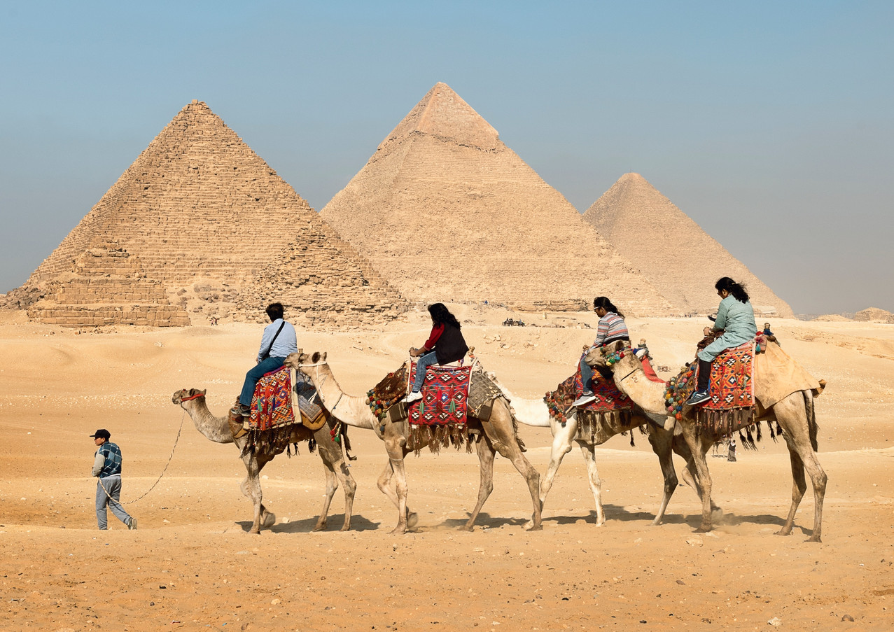 four-people-riding-on-camels-across-the-