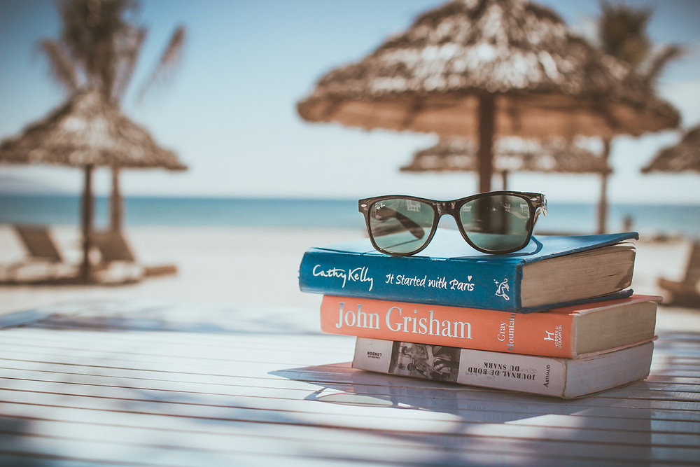 A stack of three books that will be read during vacation, on a table at a beach with thatched umbrellas.