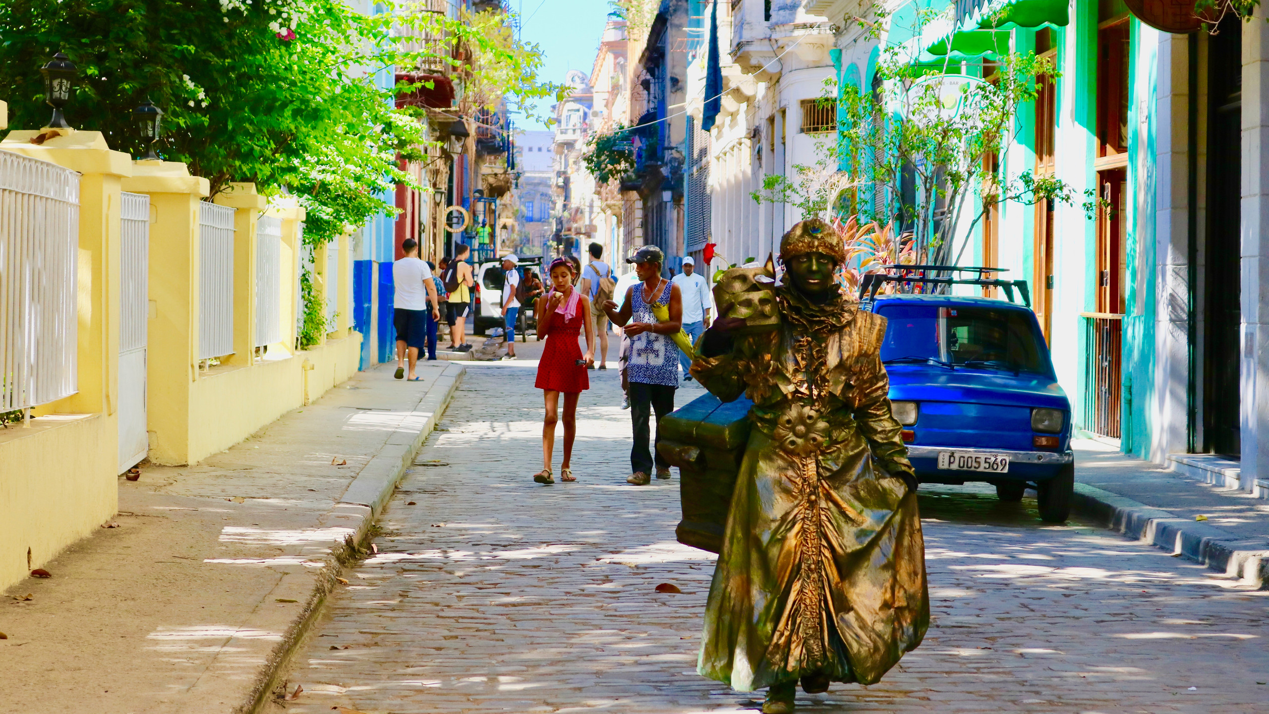 Golden living statue walking down a cobblestone street in Old Havana.