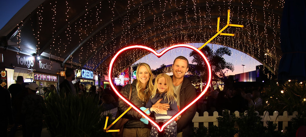 Family of three framed in light-up heart photo op in Eat Street in Brisbane, Australia