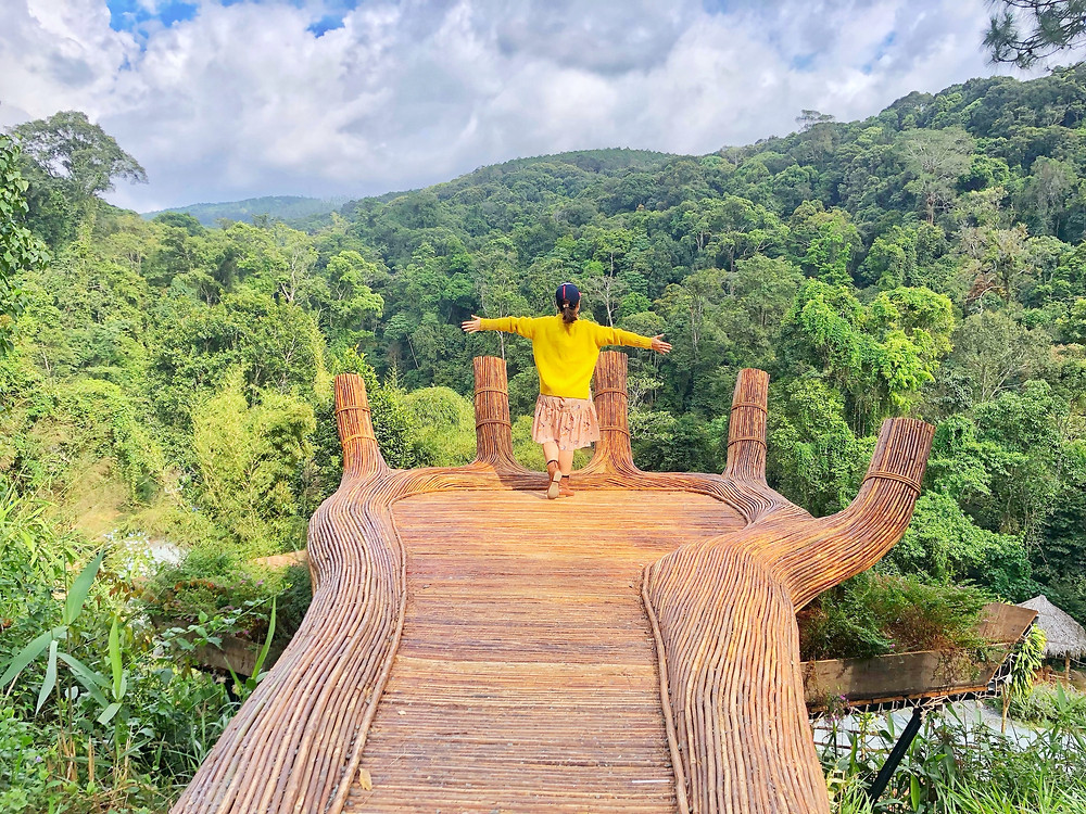 Woman in yellow sweater standing on a hand made out of wood that's stretched out above an eco-friendly resort during a luxury vacation.