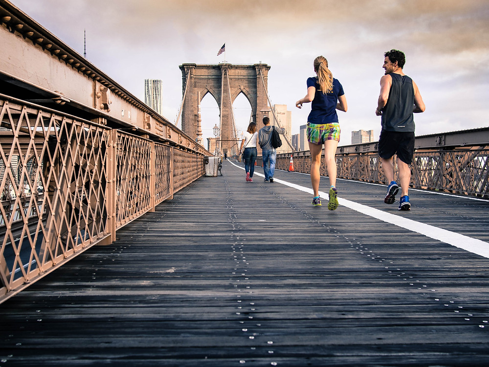 A man and woman jogging across a bridge to settle into vacation mode.