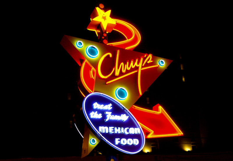 Chuy's mexican restaurant sign lit up at night.
