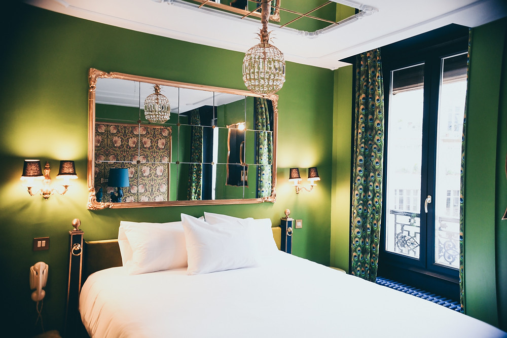Luxury hotel room in France with green walls, and a crystal chandelier above the bed.