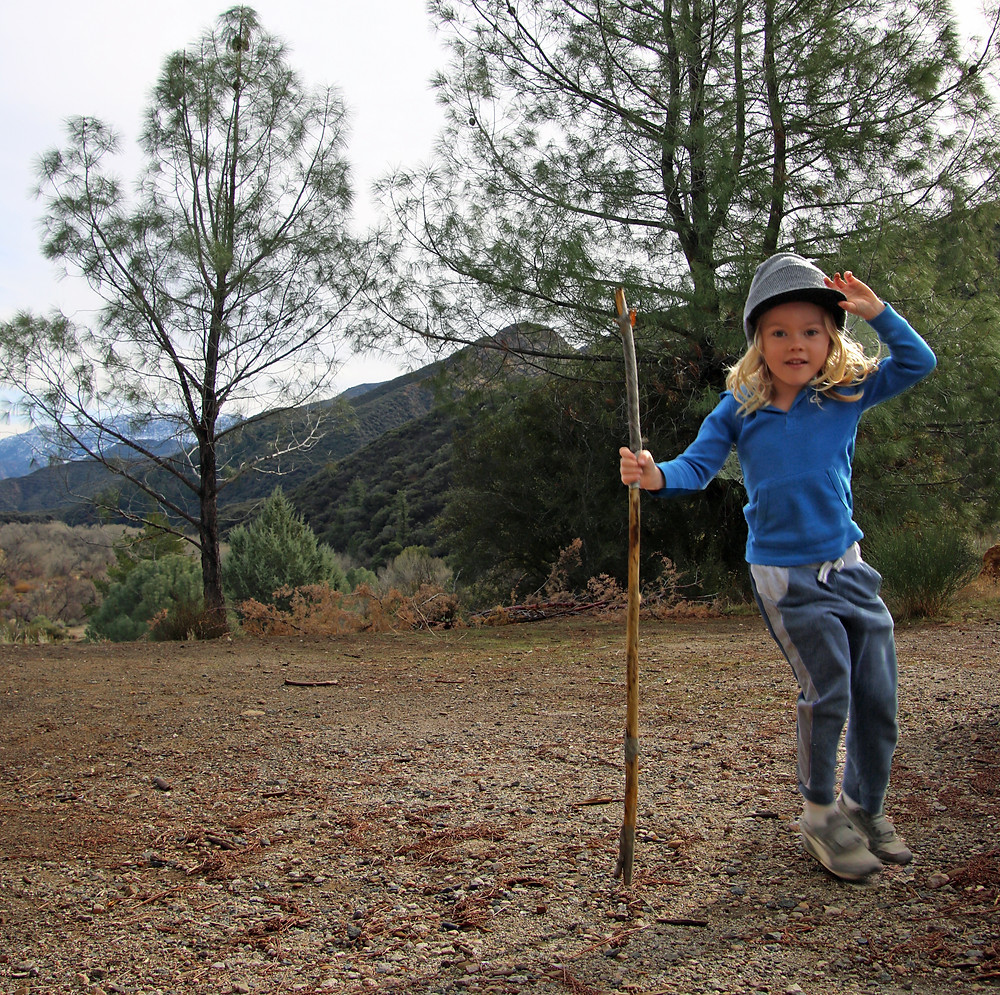 Little boy in sweatpants, a blue shirt and a beanie holding a hiking stick and dancing on the trail to Piedras Blancas in Southern California.