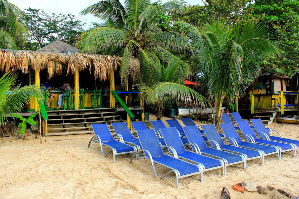 Blue lounge chairs on the beach in front of Sundowners bar and restaurant in Roatan's West End.