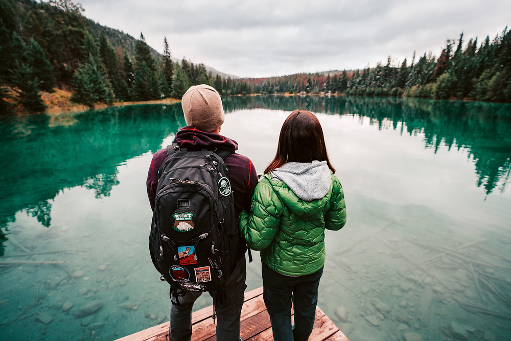 Man in crimson sweater and beanie standing next to a woman in a green down jacket on the edge of a dock above a clear, turquoise lake.