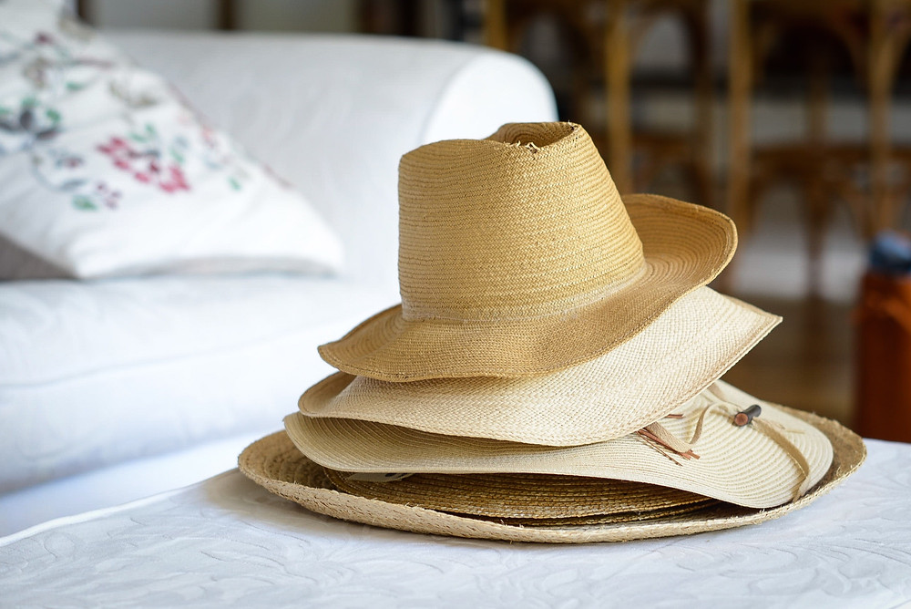 Stack of woven and straw hats on a white loveseat.
