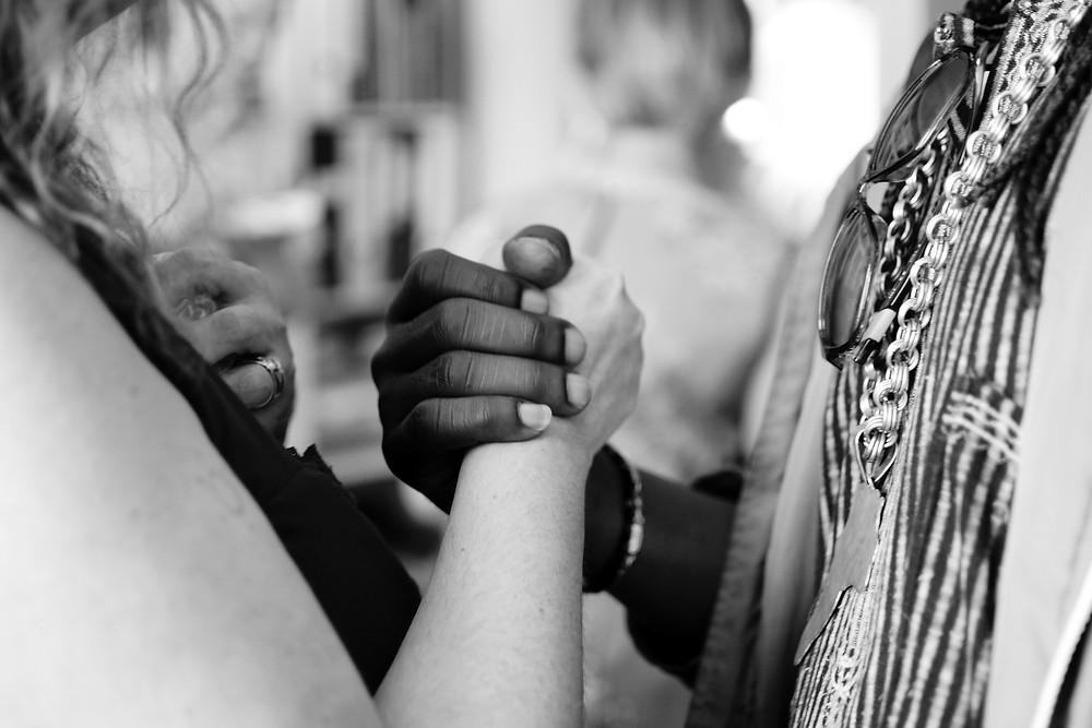 Two women holding hands in an act of kindness while on a volunteer trip