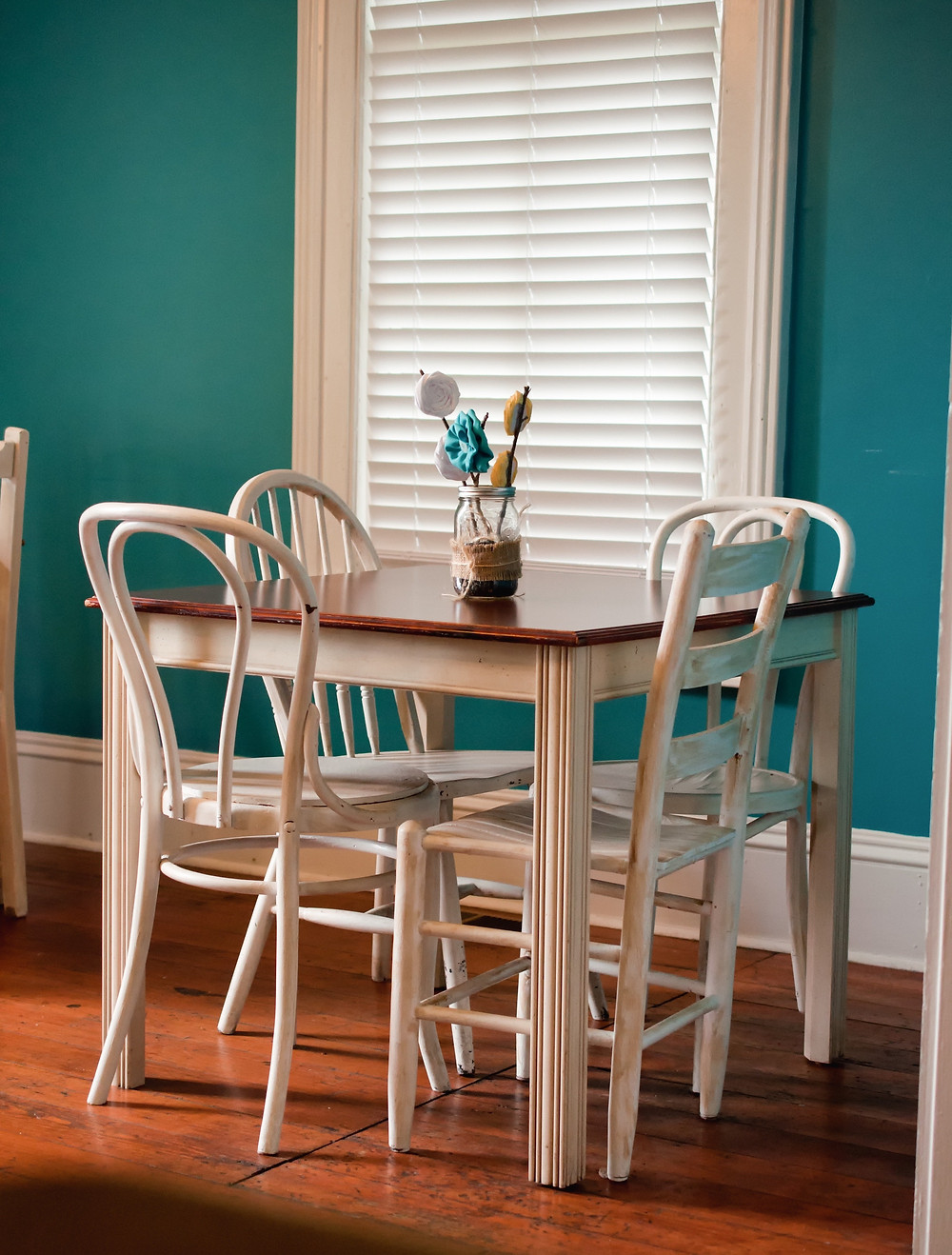 A kitchen with a small table and chairs, and the blinds closed because the family is on a trip
