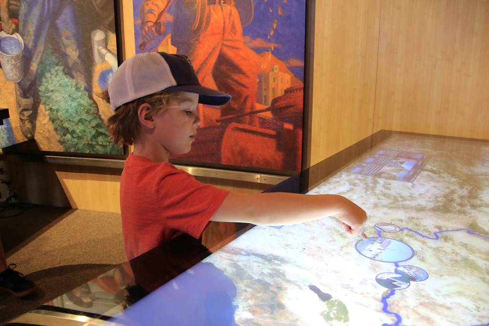 A blonde boy in a baseball hat pointing to a point on the map as he prepares for a trip.