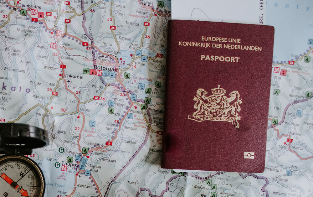 Red, European passport sitting on top of a map, next to a compass.