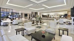 Sleek white and black lobby in Havana's luxury Melia Cohiba hotel.