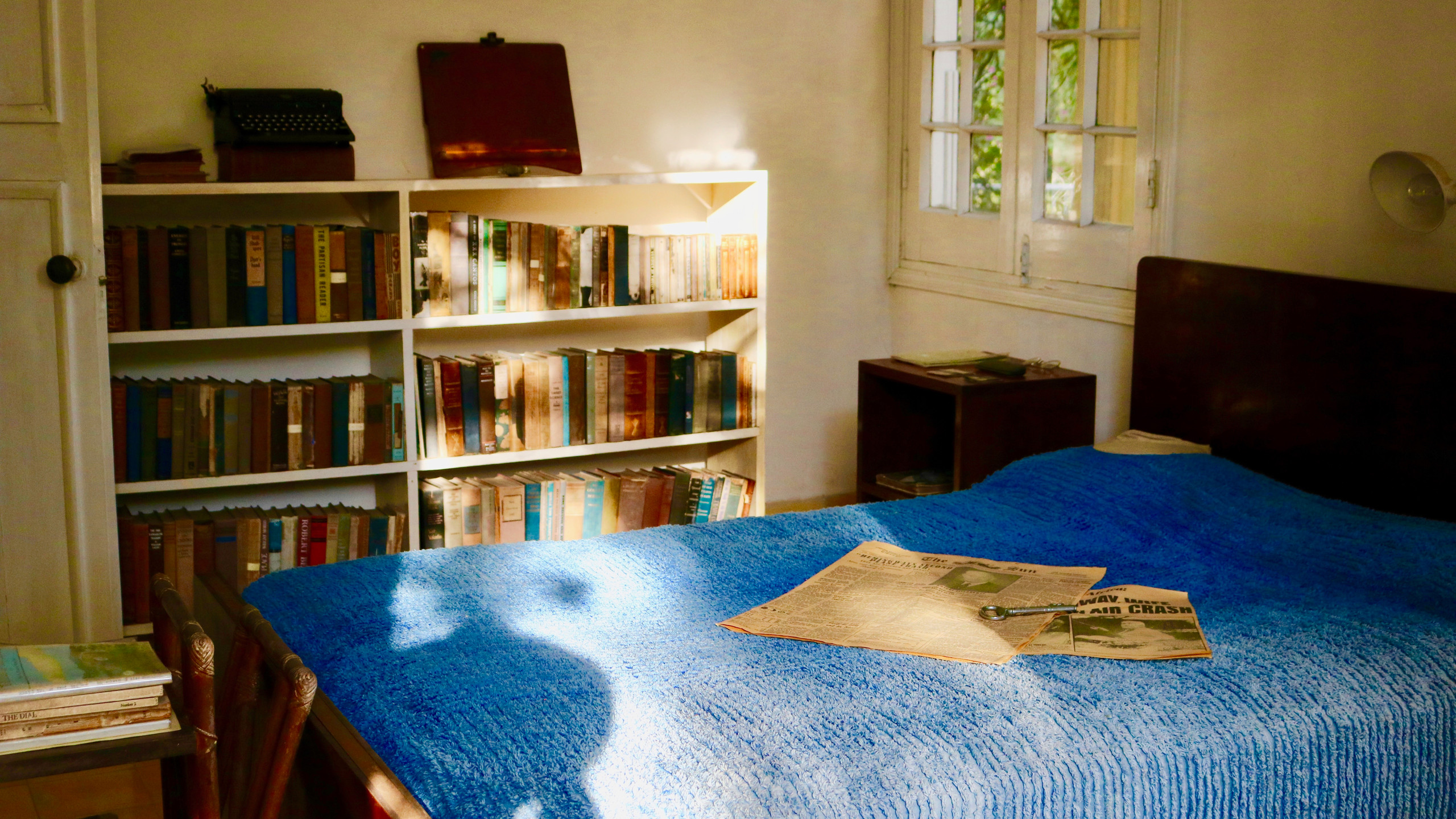 Guest room with a bed with a blue blanket and old newspaper on it at Ernest Hemingway's Finca Vigia.
