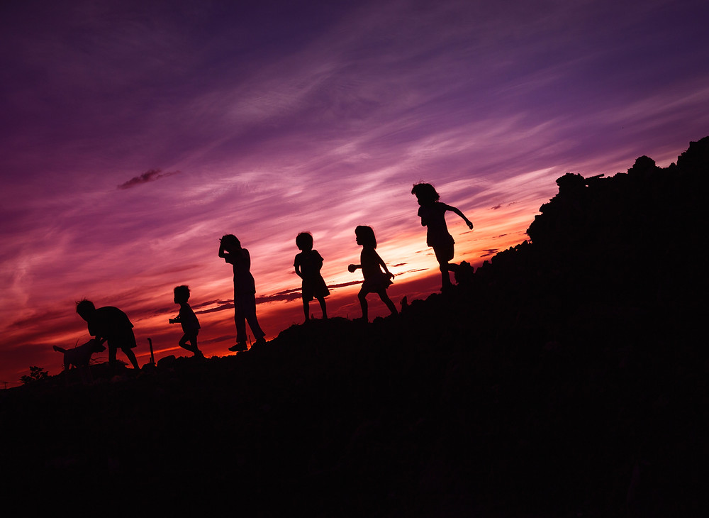 Children playing outside at sunset during a family vacation