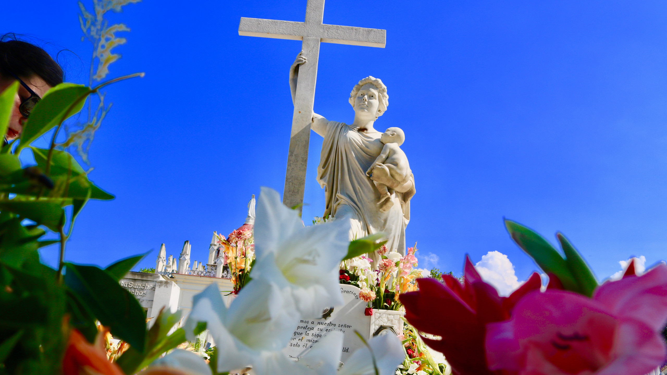 La Milagrosa grave and a close-up of the fresh flowers in it in Havana's Colon Cemetery.