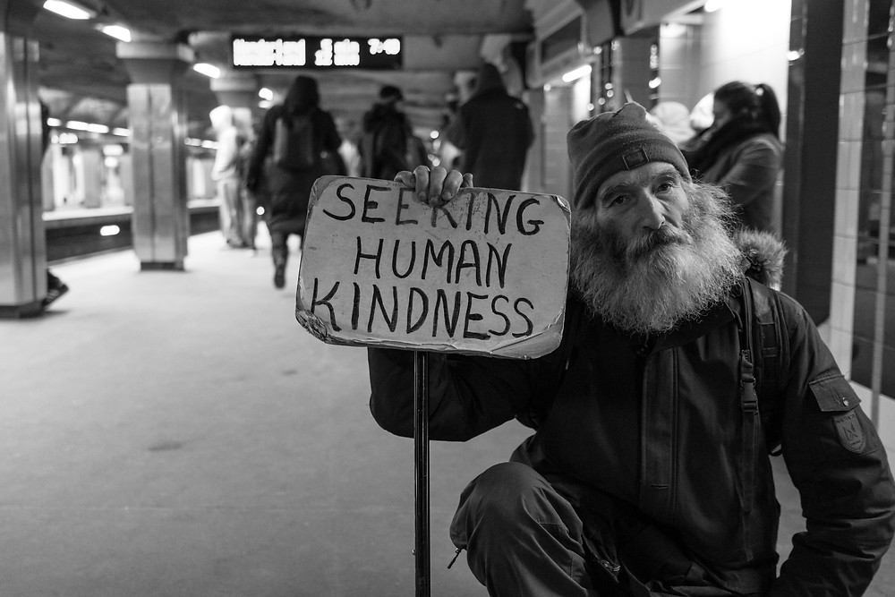 Homeless man in the subway holding a sign that says seeking human kindness