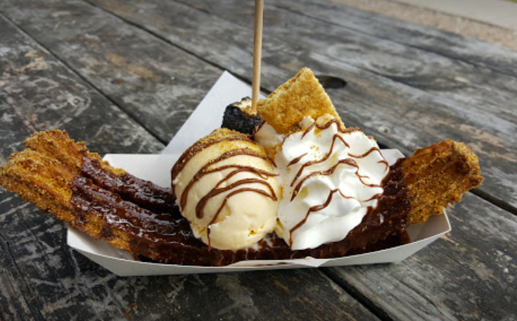 Two churros topped with ice cream and whipped cream on a picnic table at Churro Co. in Austin.