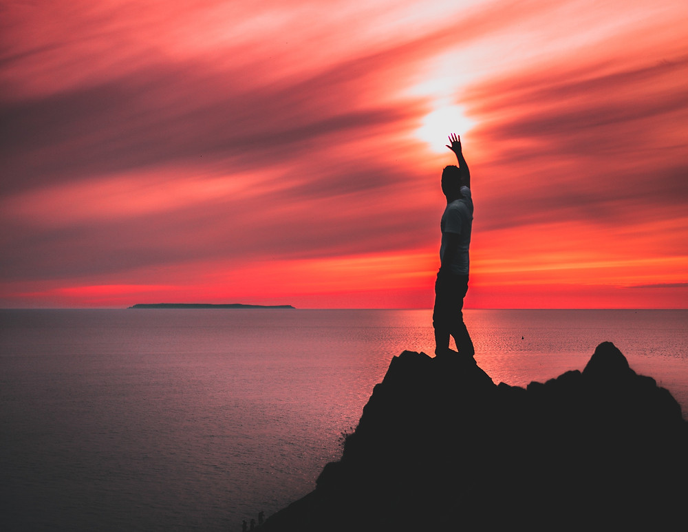 Traveling man standing on a rock by the ocean at sunset with his hand raised toward the sun