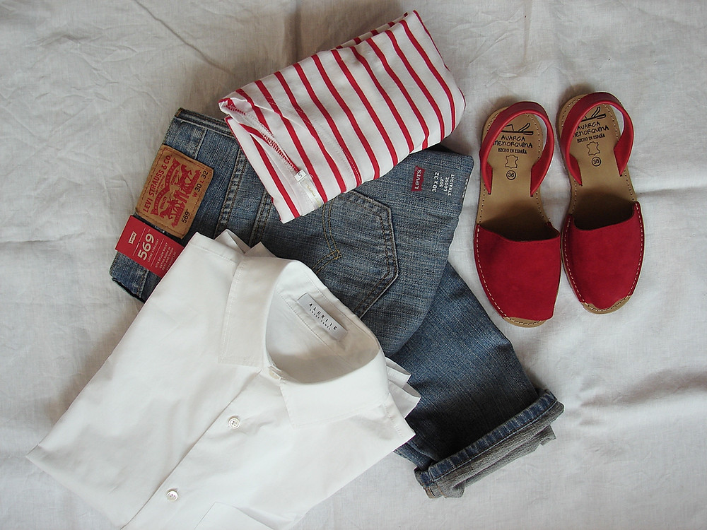 Outfit with jeans, a white shirt and red shoes that are on a beach vacation packing list