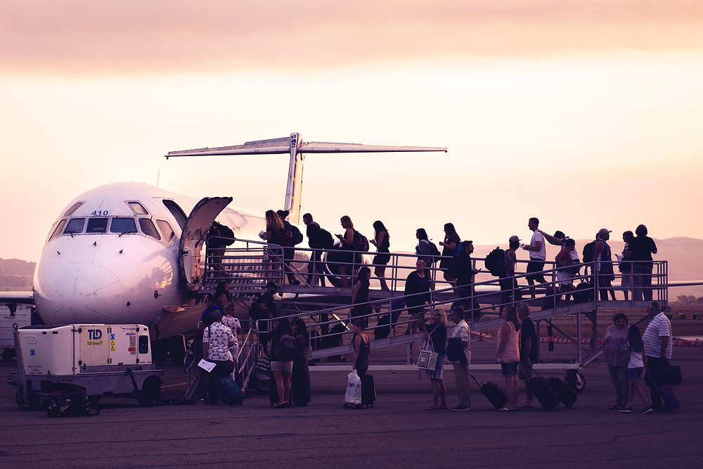 People boarding a white plane from the tarmac.