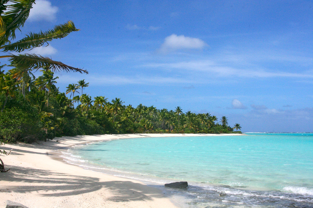 Deserted white sand beach, backed by palm trees, on the Cook Islands in the South Pacific.