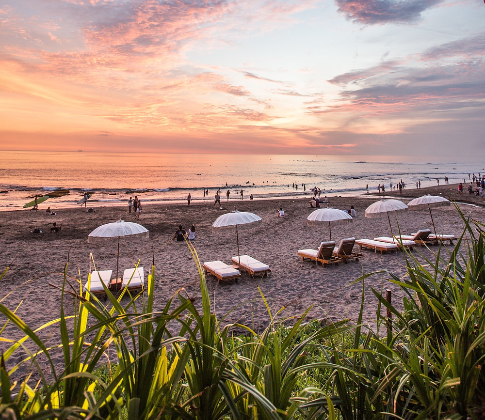 White lounge chairs and umbrellas on a wide beach in Canggu, Bali.