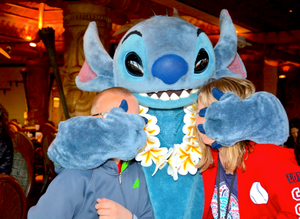 Stitch from Lilo and Stitch covering the eyes of two children at a Disney World character meal