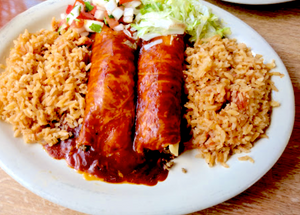 Two enchiladas smothered in red sauce on a white plate with rice at Habanero restaurant.