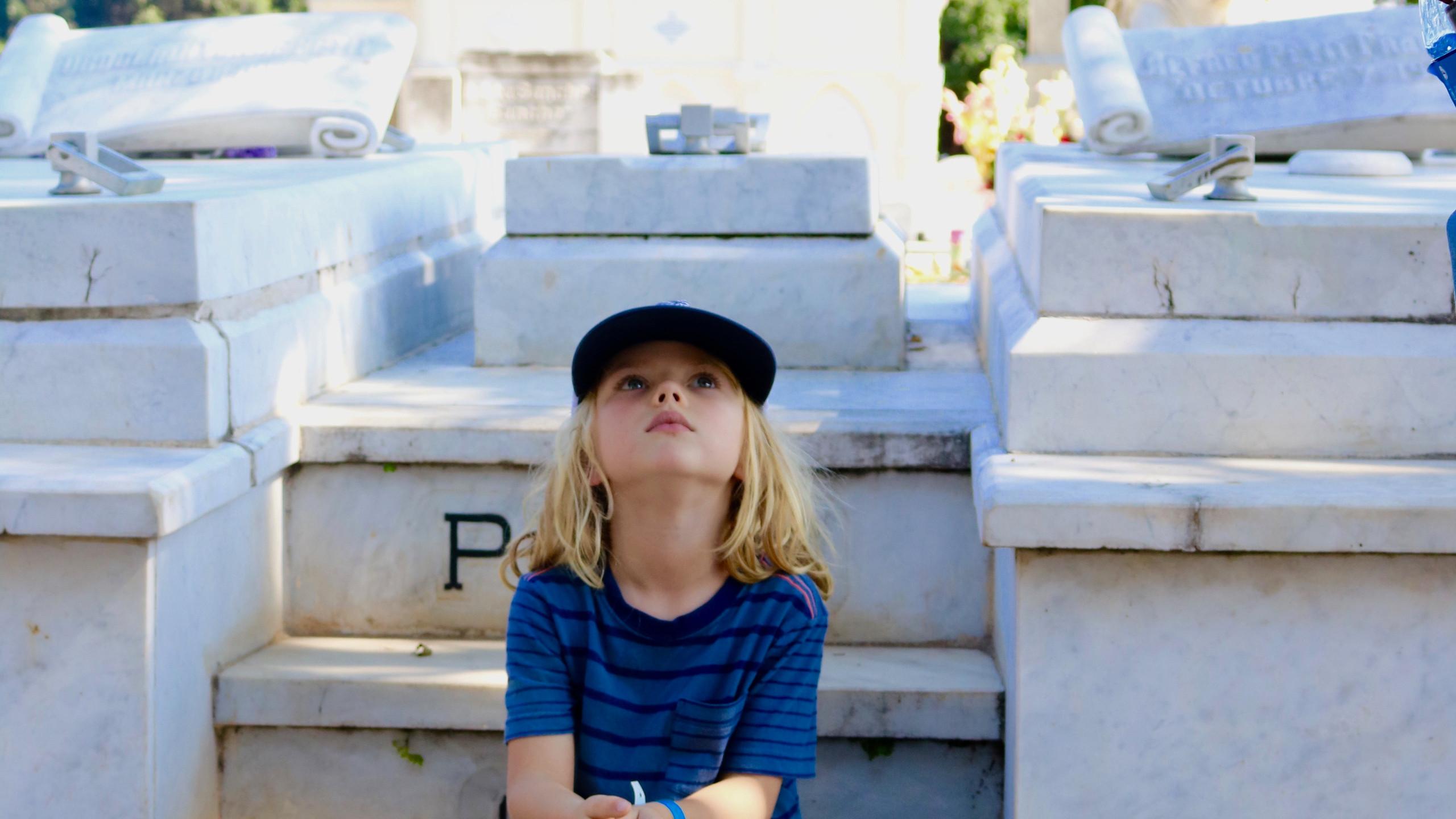Little boy in blue striped shirt sitting on steps in Havana's Colon Cemetery.