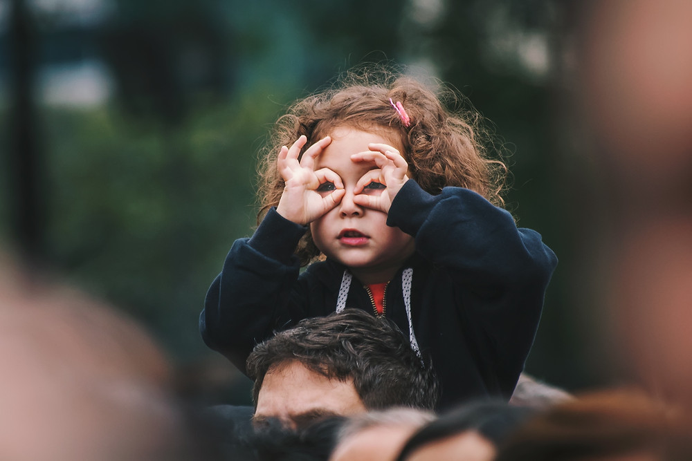 A little girl with red hair on her father's shoulders playing eye spy while on a trip