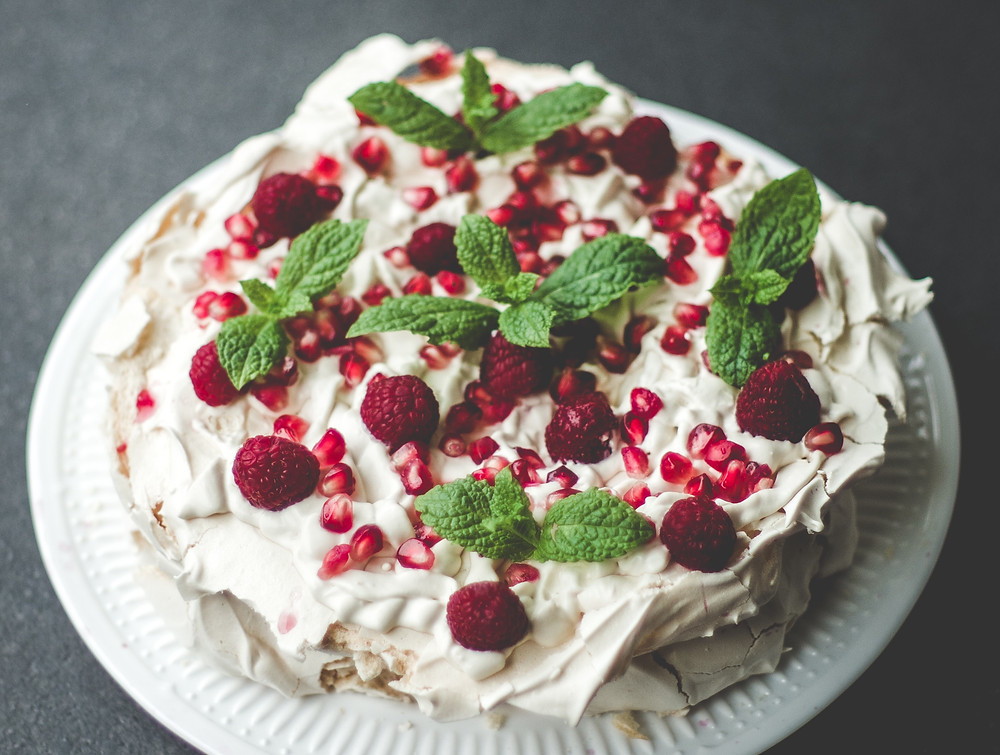 Pavlova cake with raspberries, pomegranate seeds and mint in Australia