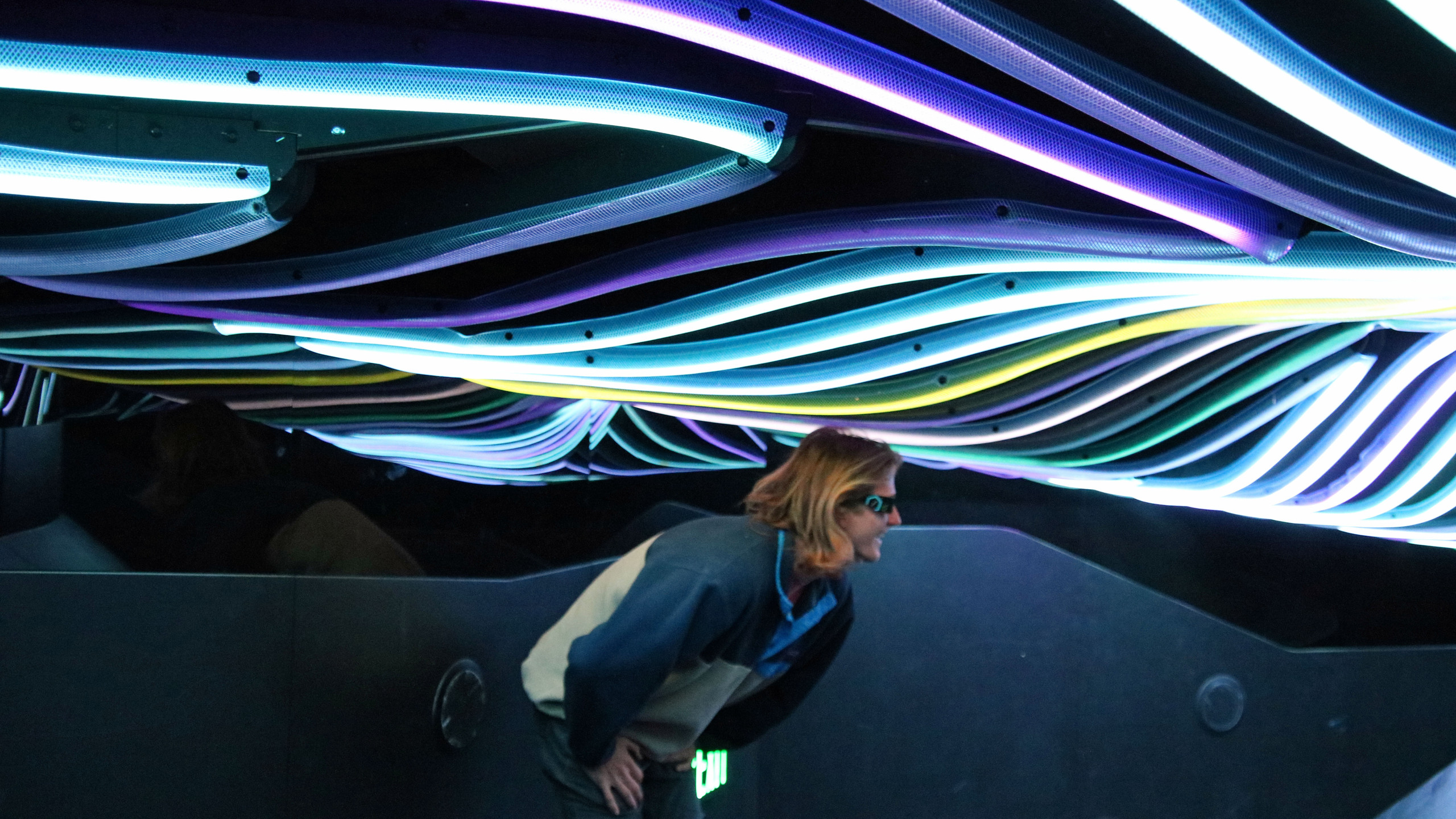 Man crouched in a room with a low ceiling covered in lights