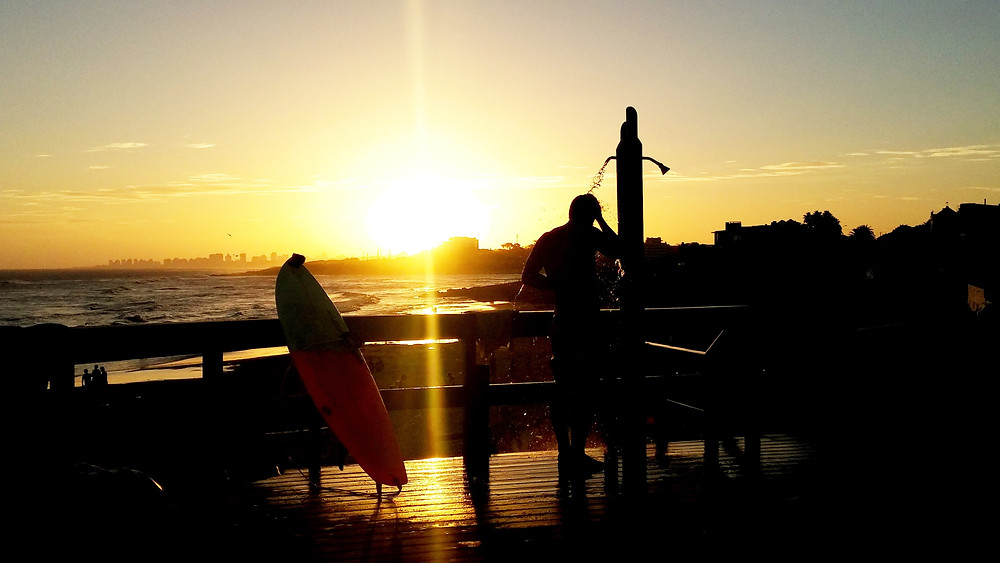 Aussie surfer showering at sunset next to the beach