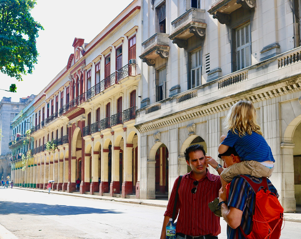 Cuban man with red shirt talking to a man in a blue striped shirt with a red back and little blonde boy on his shoulders on a street in Havana.