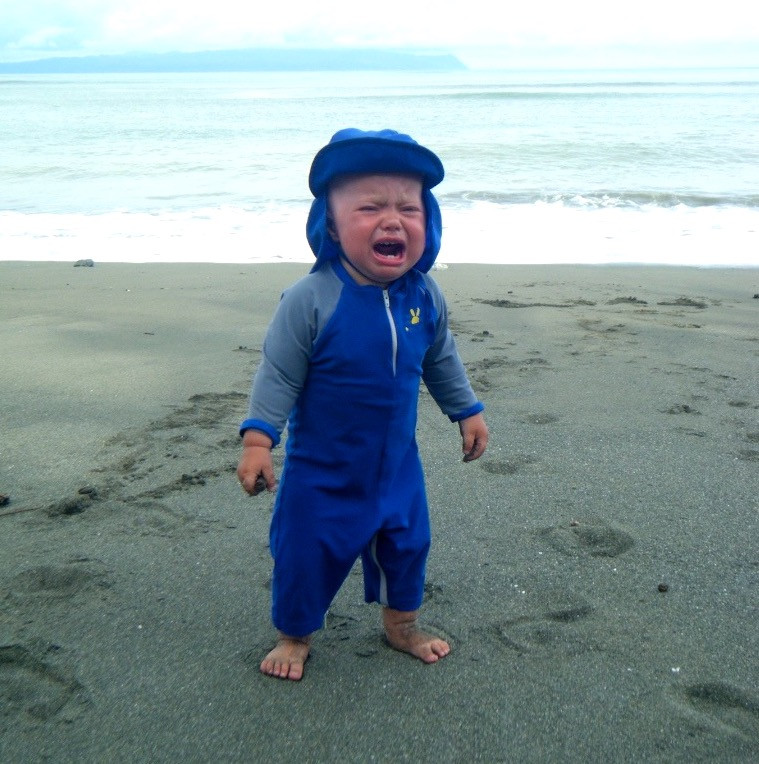 A baby in a blue sunsuit and hat crying on a beach in Costa Rica's Osa Peninsula