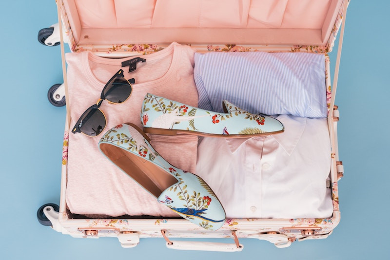 Pink suitcase filled with pink clothing, sunglasses and blue flats with flowers on them for an amusement park vacation