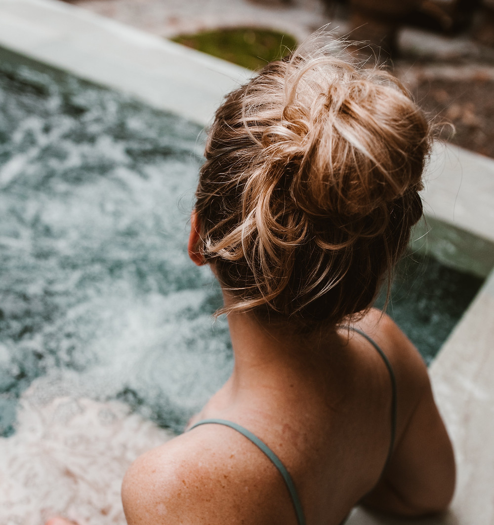 A blonde woman in a hot tub pampering herself during vacation.