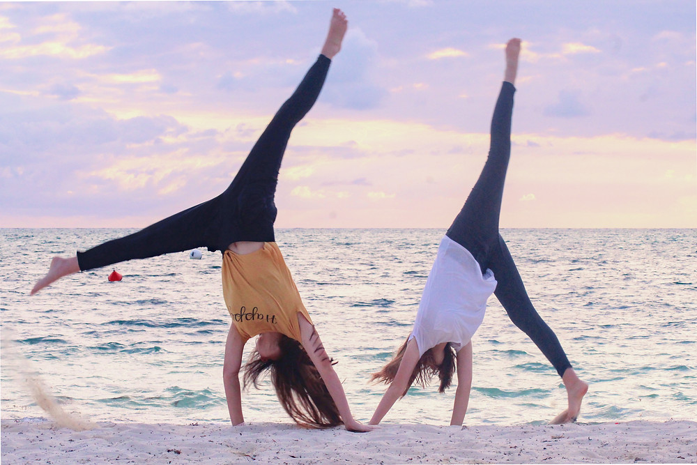 Two women doing yoga on the beach during a surf trip