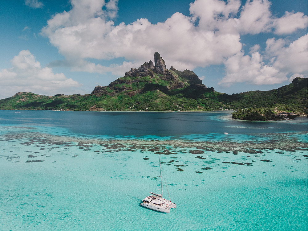 A catamaran in the clear, sky-blue water of Bora Bora that's backed by a lush mountain with a rocky spire.