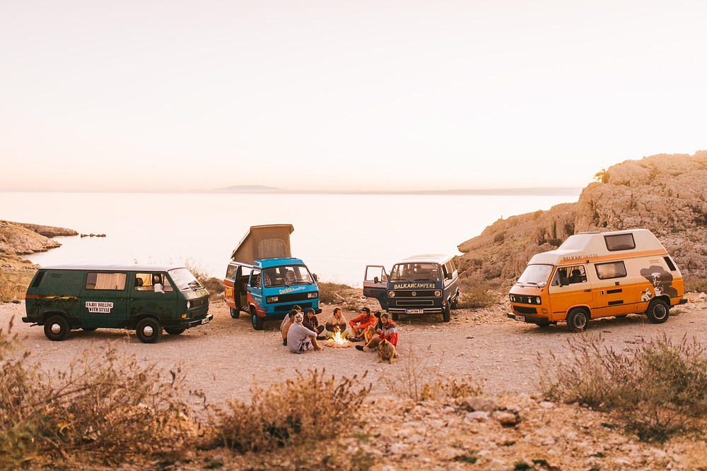 4WD vans on the beach and surfers around a campfire