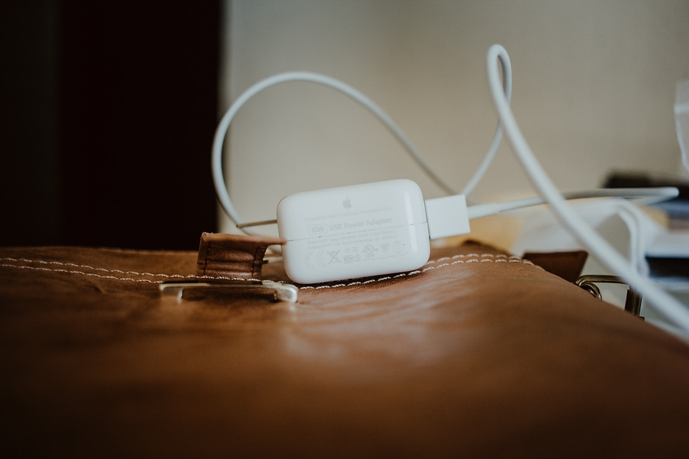 Cell phone and laptop charger on a brown leather briefcase