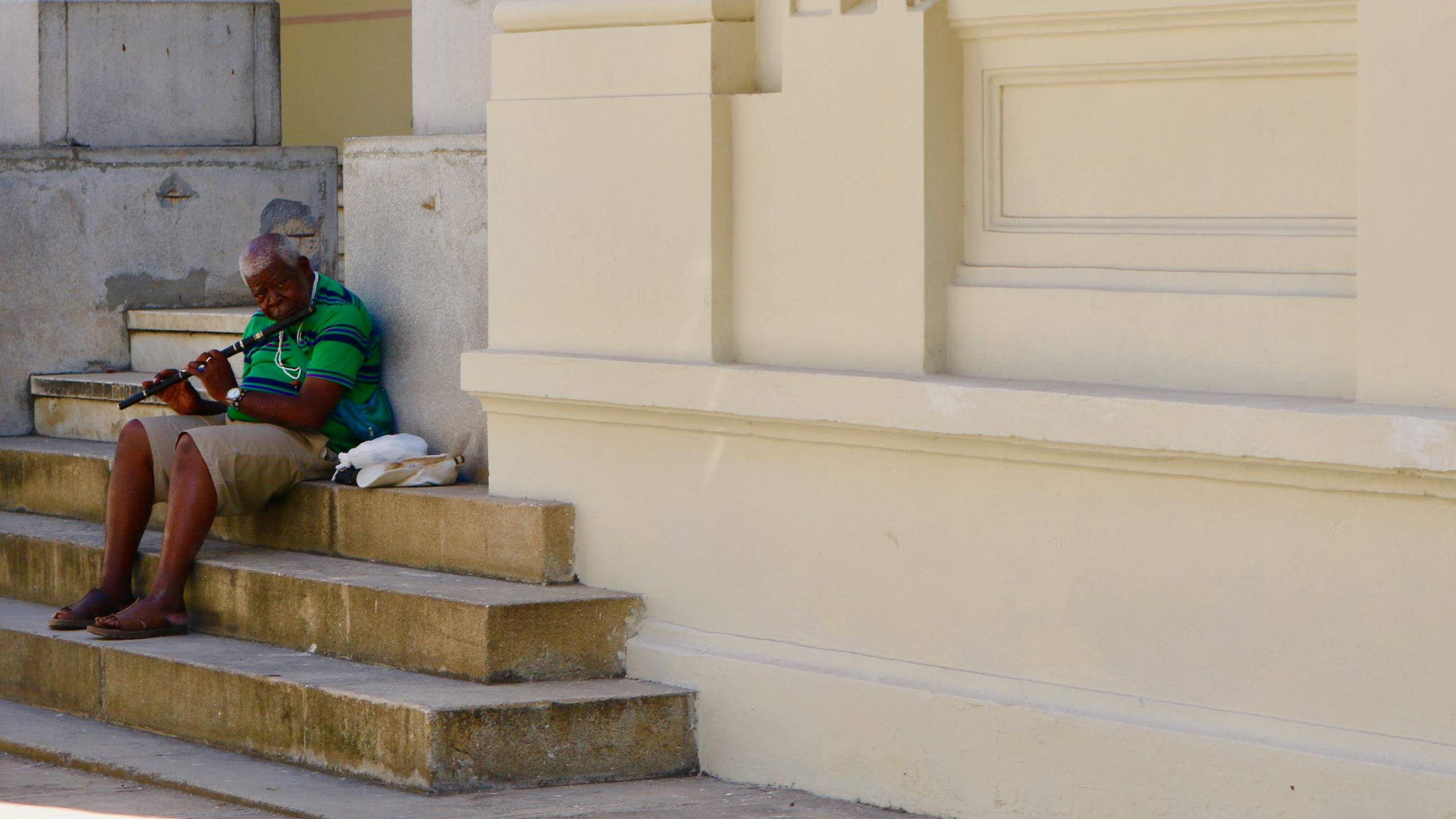 Old Cuban man in a green shirt and khaki shorts sitting on steps and playing a flute in Old Havana.