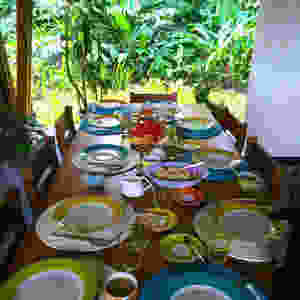 Outdoor dining room table in Costa Rica's Osa Peninsula set with dishes, eggs and fresh fruit