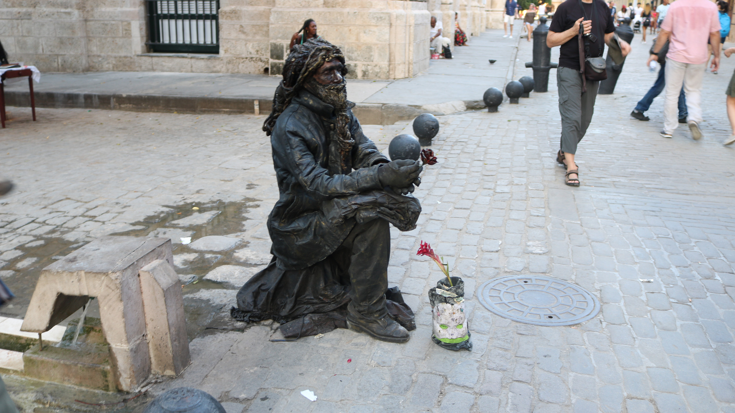 Living statue sitting on a street in Old Havana with a tip can with a red flower in it in front of him.