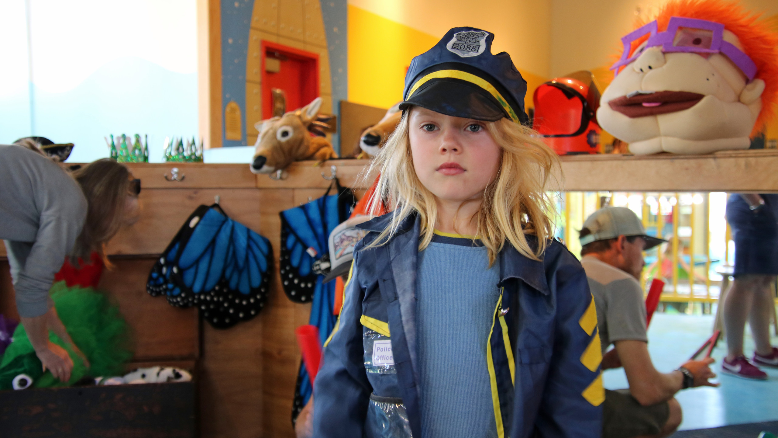 Blonde boy in a blue police uniform costume in the dress up area of the Santa Fe Children's Museum